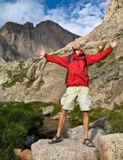 Hiker at feeling the sunrise below Longs Peak in Rocky Mountain National Park